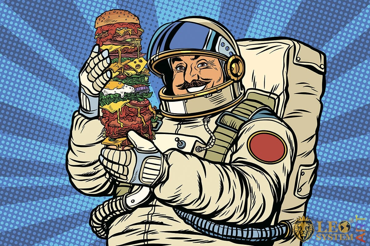 Picture of a hungry astronaut with a huge burger in his hands