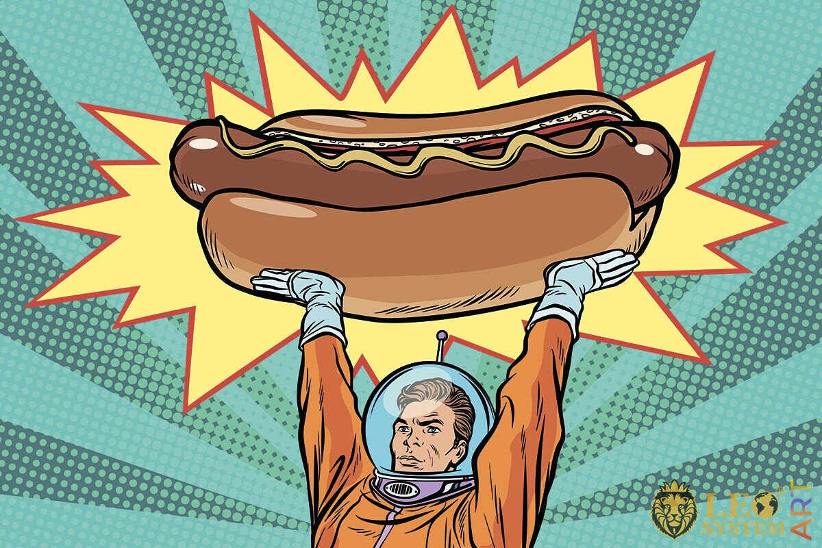 Astronaut holds a large hot dog above his head