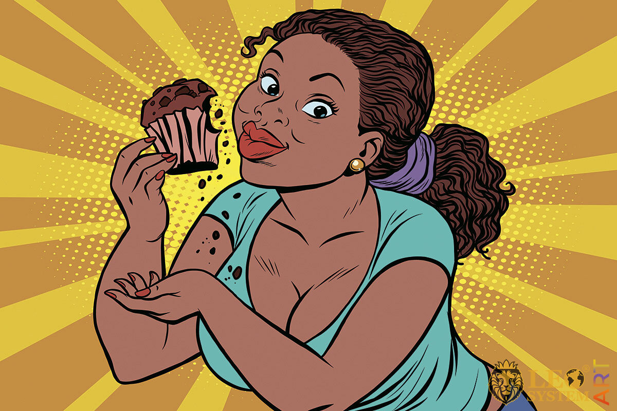 Picture of a hungry woman with a cupcake in her hands