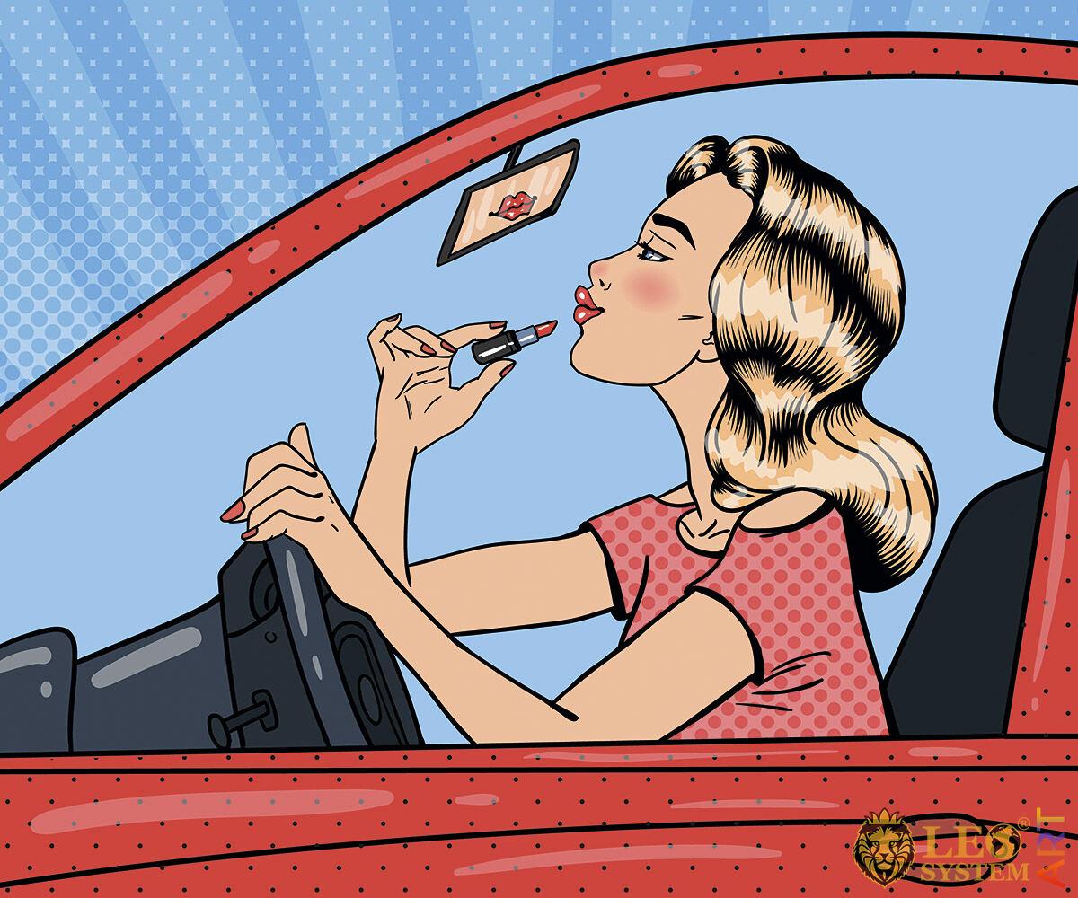 Pretty woman paints lips in auto